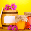 Sweet honey in jars and barrel with drizzler on wooden table on yellow background - Stock Photo