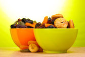 Dried fruits in bright bowls on wooden table on green background — Stock Photo