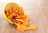 Tasty potato chips in green bowl on wooden table — Stock Photo