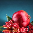 Ripe pomegranate fruit with leaves on blue background — Stock Photo #9302815