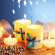 Beautiful candles, gifts and decor on wooden table on blue background — Stock Photo #9303188