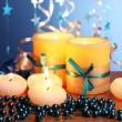 Beautiful candles, gifts and decor on wooden table on blue background — Stock Photo #9303209