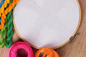 The embroidery hoop with canvas and bright sewing threads for embroidery in the table — Stock Photo