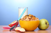 Tasty cornflakes in yellow bowl, apples and glass of milk on wooden table on blue background — Stock Photo