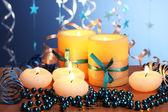Velas bonitas, presentes e decoração na mesa de madeira em fundo azul — Foto Stock