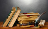 Old books, scrolls, feather pen and inkwell on wooden table on grey background — Stock Photo