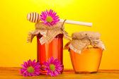 Sweet honey in jars with drizzler on wooden table on yellow background — Stock Photo