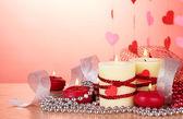 Kaarsen voor Valentijnsdag op houten tafel op rode achtergrond — Stockfoto