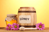 Sweet honey in barrel and jar with drizzler on wooden table on yellow background — 图库照片
