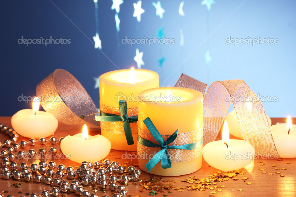 Beautiful candles, gifts and decor on wooden table on blue background  Stock Photo #9303188