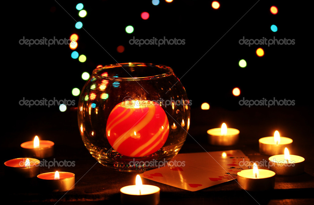 Candles and playing cards on wooden table on bright background  Stock Photo #9303375