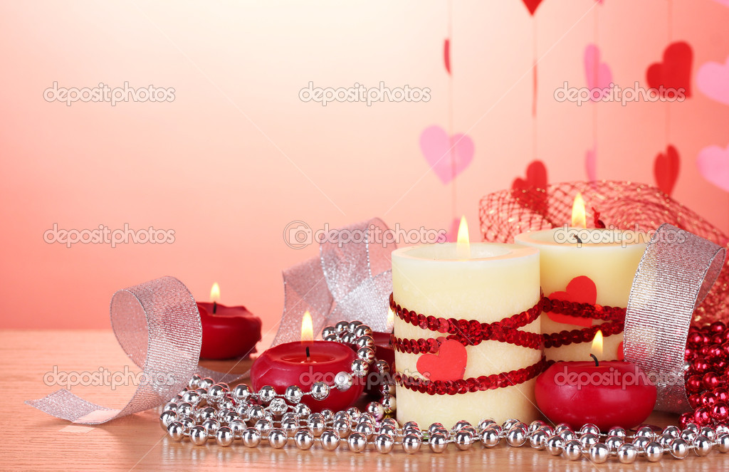 Candles for Valentine's Day on wooden table on red background — Stock Photo #9305600