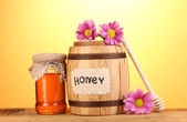Sweet honey in barrel and jar with drizzler on wooden table on yellow background — Stockfoto