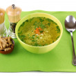Stock Photo: Tasty chicken stock with noodles on green tablecloth