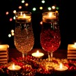 Stock Photo: Amazing composition of candles and glasses on wooden table on bright background