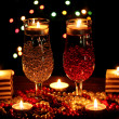 Amazing composition of candles and glasses on wooden table on bright background - Stockfoto