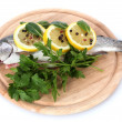 Royalty-Free Stock Photo: Fresh fish with lemon, parsley and pepper on wooden cutting board isolated on white