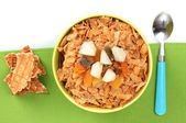 Tasty cornflakes in bowl with dried fruits on green napkin — Stock Photo