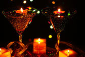 Amazing composition of candles and glasses on wooden table close-up on bright background — Stockfoto