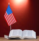 Bandeira americana sobre o carrinho e livros sobre a mesa de madeira em fundo vermelho — Foto Stock