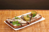 Tasty sandwiches with sprats on plate on wooden mat on brown background — Stock Photo