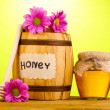 Sweet honey in barrel and jar with drizzler on wooden table on green background — Stock Photo