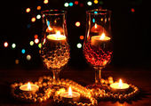 Amazing composition of candles and glasses on wooden table on bright background — Stok fotoğraf