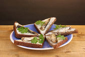 Tasty sandwiches with sprats on plate on wooden table on brown background — Stock Photo