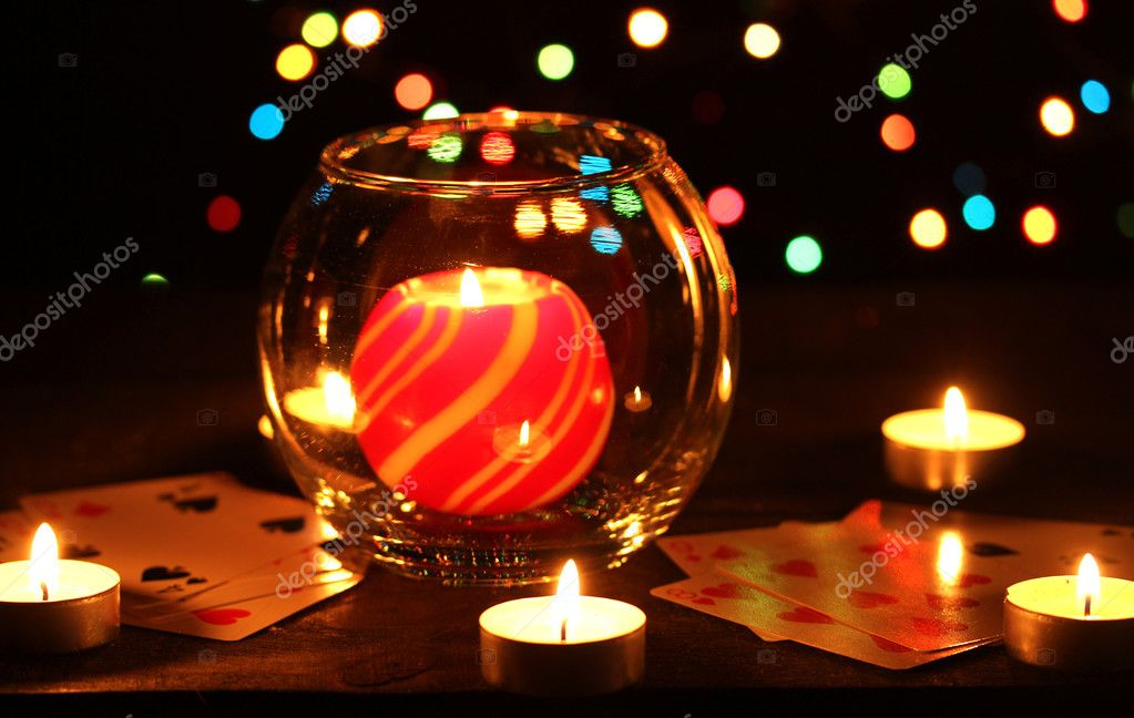 Candles and playing cards on wooden table on bright background — Stock Photo #9373440