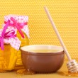 Royalty-Free Stock Photo: Jars of honey, bowl and wooden drizzler with honey on yellow honeycomb background
