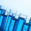 Test-tubes with blue liquid on blue background - Foto Stock