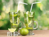 Glasses of cocktail with lime and mint on wooden table on green background — Stock Photo
