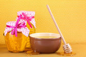 Jars of honey, bowl and wooden drizzler with honey on yellow honeycomb background — Stock Photo