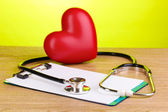 Medical stethoscope with clipboard and heart on wooden table on green background — Stock Photo