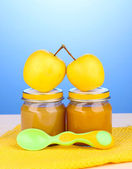 Jars of baby puree with spoon on napkin on blue background — ストック写真