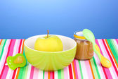 Jar of baby puree with plate and spoon on napkin on blue background — Stock Photo