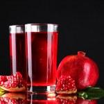 Ripe pomergranate and glasses of juice on black background — Stock Photo #9405365