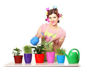 Beautiful happy young housewife sprays plants in flowerpots isolated on white — Stock Photo