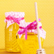 Jars of honey and wooden drizzler on yellow honeycomb background — Stock Photo #9416701