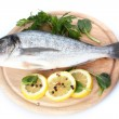 Fresh fish with lemon, parsley and spice on wooden cutting board isolated on white — Stock Photo