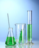 Laboratory glassware with green liquid with reflection on blue background — Stock Photo