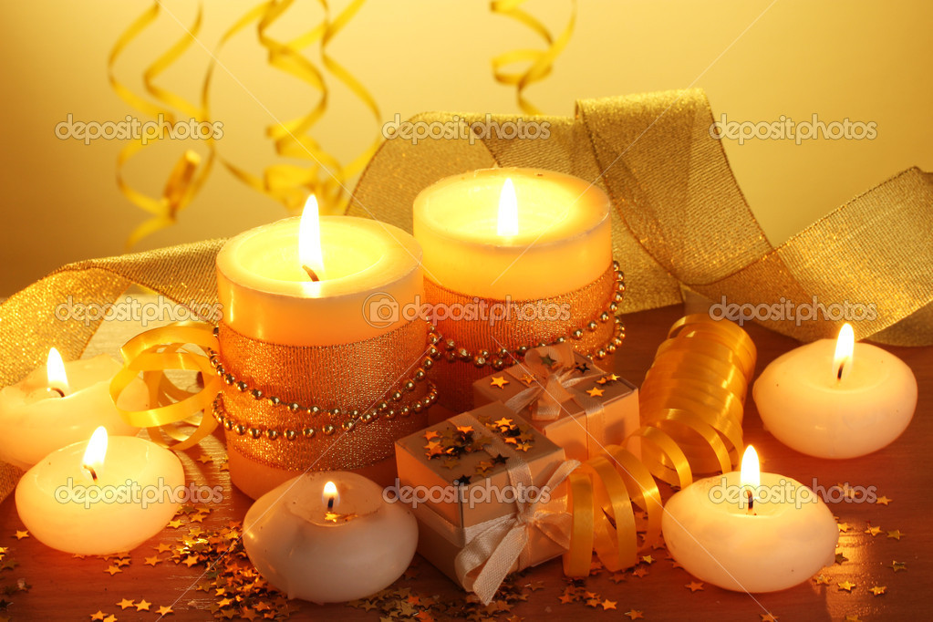 Beautiful candles, gifts and decor on wooden table on yellow background  Stock Photo #9457555
