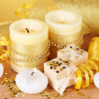 Beautiful candles, gifts and decor on wooden table on yellow background — Stock Photo