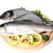 Fresh fishes with lemon, parsley and spice on wooden cutting board isolated on white - Стоковая фотография