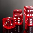 Red dices on grey background - Stock Photo