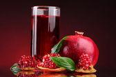 Pomergranate madura e copo de suco em fundo vermelho — Foto Stock