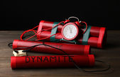 Timebomb made of dynamite on wooden table on black background — Stock Photo