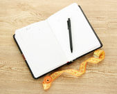 Pianificazione della dieta. taccuino di misura nastro e penna sul tavolo di legno — Foto Stock