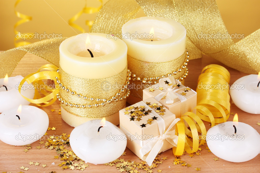 Beautiful candles, gifts and decor on wooden table on yellow background  Stock Photo #9470818