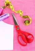 Scissors,threads, measuring tape and pattern on fabric close-up — Stock Photo
